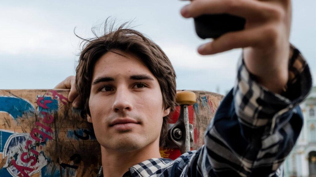 Kampagnenbild Lebara. Junge mit Skatboard hält sich ein Handy vor das Gesicht