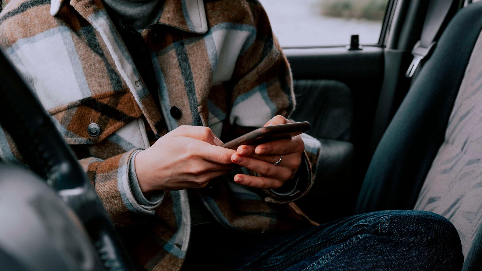 Eine Frau sitzt im Auto und hält ein Handy in der Hand